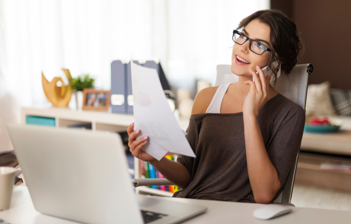 Smiling Woman on Phone with Laptop Working from Home