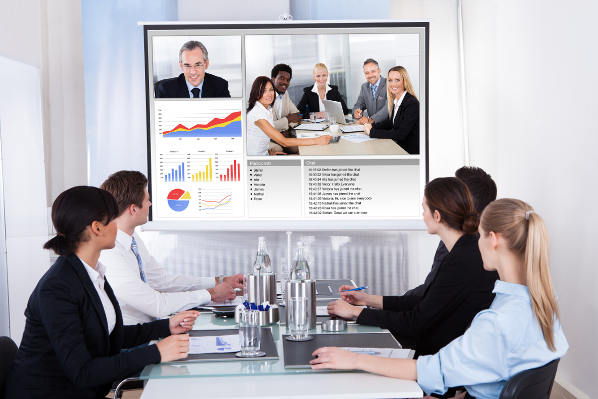 Group of Business People Seated Around Meeting Table Looking at Video Conference Screen