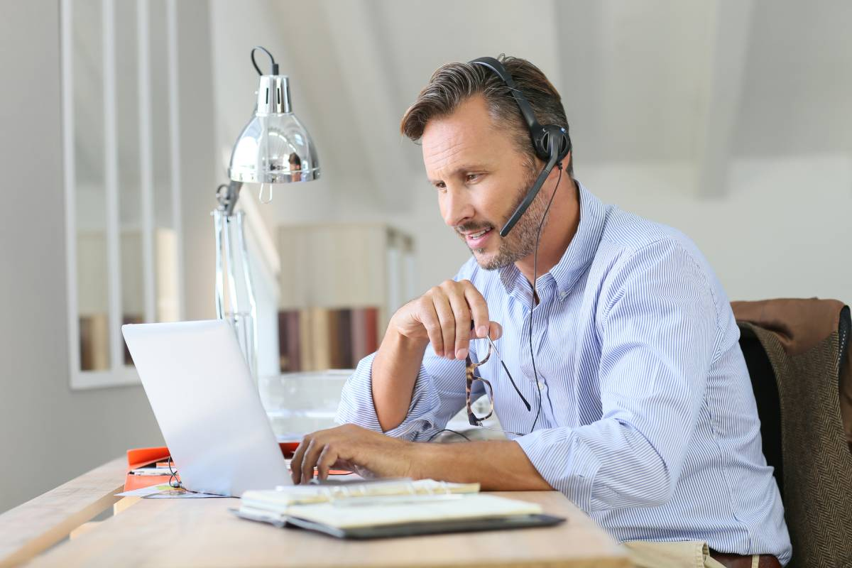A man working from home using a headset and a laptop